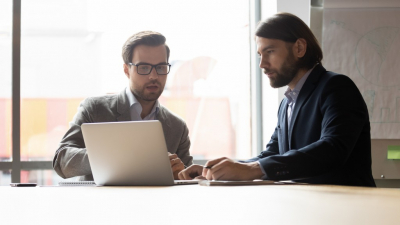 businessman wearing glasses consulting client about insurance or loan, pointing at laptop screen, two colleagues employees working on project together, discussing strategy, sharing ideas